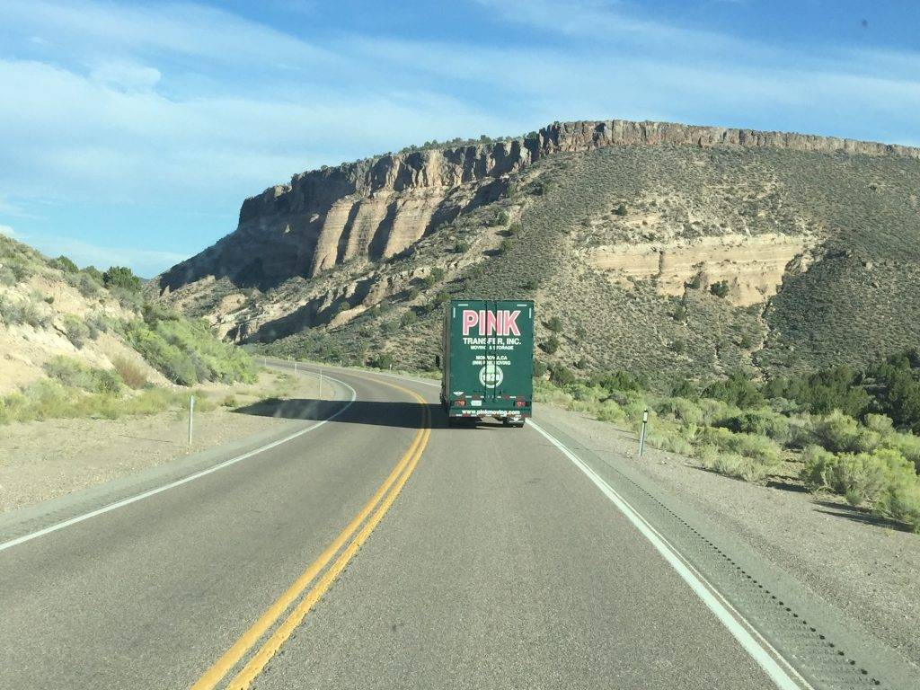 pink moving truck driving in the mountains